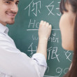 Teacher with student in front of chalkboard writing — Stock Photo