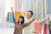 Couple posing with shopping bags — Stock Photo
