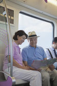 Mature couple sitting in the subway and looking at the map — Stock Photo