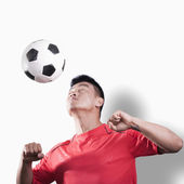Footballer heading the ball — Stock Photo
