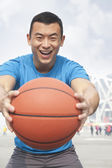 Young man holding a basketball — Stock Photo