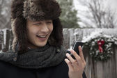 Man in Fur Hat Looking at Cell Phone — Stock Photo