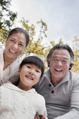 Grandparents and granddaughter in park — Stock Photo