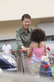 Daughter and mother with shopping cart — Stockfoto