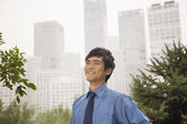 Businessman smiling in the park — Stock Photo