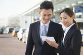 Travelers looking at ticket in airport — Stock Photo