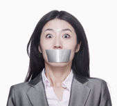 Businesswoman with her mouth caver with duct tape — Stock Photo