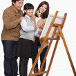 Girl painting with parents — Stock Photo