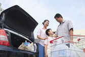 Family talking next to the car with shopping bags — Stock Photo