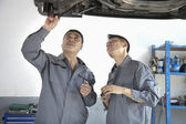Two Mechanics Looking at Underside of a Car — Stock Photo
