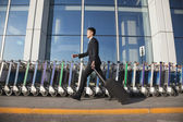 Traveler walking fast next to row of luggage carts — Stock Photo