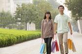 Couple marchant avec des sacs à provisions en mains — Photo