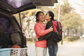 Mother and daughter embracing behind car on college campus — Stock Photo