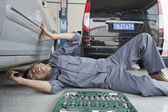 Mechanic Working on Underside of Car — Stock Photo