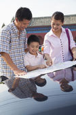 Family standing next to the car and looking at the map — Stock Photo