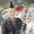 Man with punk Mohawk holding guitar — Stock Photo #36400229