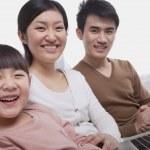 Family sitting on the sofa using laptop — Stock Photo #36400279