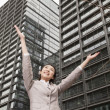 Businesswoman with arms outstretched among skyscrapers — Stock Photo