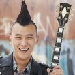 Man with punk Mohawk holding guitar — Stock Photo