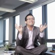 Businessman sitting on desk in the office meditating — Photo