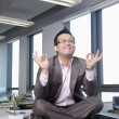Businessman sitting on desk in the office meditating — Stockfoto