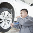 Stock Photo: Mechanic Adjusting Tire