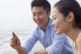 Couple looking at seashell at the waters edge — Stock Photo
