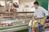 Man standing and looking at the Deli counter — Stock Photo