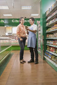 Sales clerk assisting woman in the supermarket — Stockfoto