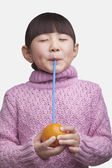 Girl drinking an orange with a straw — Stock Photo