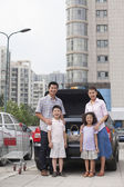 Family standing next to the car with shopping bags — Stock Photo