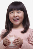 Girl drinking a glass of milk with a milk moustache — Stock Photo