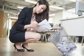 Businesswoman reading piece of paper from the trash can — Stock Photo