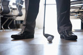 Businessman playing golf in his office — Stock Photo