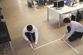 Businessmen taping up the floor in the office — Stock Photo