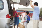 Family taking stuff out from the car — Stock Photo