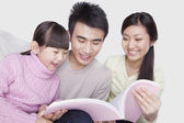 Family reading on the sofa — Stock Photo