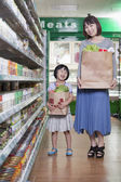 Mother and daughter holding grocery bags in supermarket — Stok fotoğraf