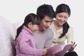 家庭在沙发上阅读 — 图库照片