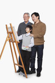 Boy painting with father and grandfather — Stock Photo