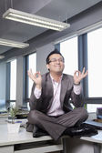 Businessman sitting on desk in the office meditating — Stock Photo