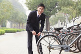 Businessman locking up his bicycle on a city street — Stock Photo