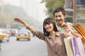 Couple with shopping bags hailing a taxicab — Stock Photo