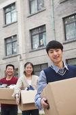 Family moving boxes into a dormitory at college — Stock Photo
