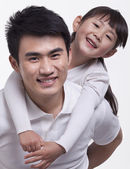 Father carrying daughter on back — Stock Photo