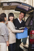 Family unpacking minivan for college — Stock Photo