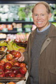 Man holding an apple in store — Stock Photo