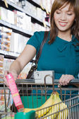 Woman putting a packet in a shopping trolley — Stock Photo