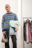Man holding clothes and handbag — Stock Photo