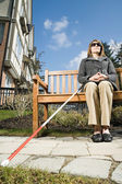 Blind woman sitting on bench — Stock Photo